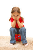 Little girl sitting on a red plastic toy. Isolated cute girl sitting on a plastic toy Royalty Free Stock Photography
