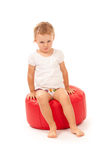 Little girl sitting on a red pouf Royalty Free Stock Photo
