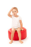 Little girl sitting on a red pouf Stock Images