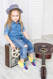 Little girl sitting on retro tape recorder and guitar lies near Royalty Free Stock Photo