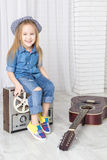 Little girl sitting on retro tape recorder and laughs Royalty Free Stock Photography