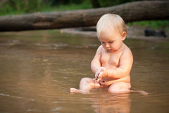 Little girl sitting in the river Royalty Free Stock Photo