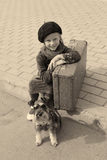 Little girl sitting on the road with a dog Stock Image