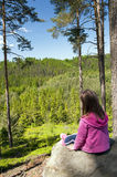 Little girl is sitting on a rock. And looking into the summer landscape royalty free stock photo