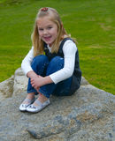 Little Girl Sitting on a Rock. A happy, smiling little girl with blond hair is sitting on a rock with her knees pulled in, held by her arms and hands, in a white royalty free stock images