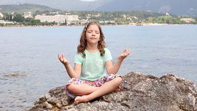 Little girl sitting on a rock and meditates stock video