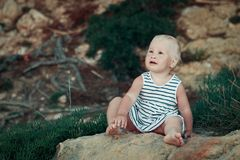Little girl sitting on rock, outdoor Stock Photo