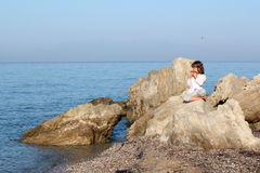 Little girl sitting on a rock and playing pan pipe. Little girl sitting on a rock by the sea and playing pan pipe Stock Photos