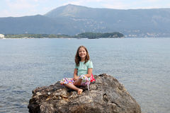 Little girl sitting on a rock by the sea. Happy little girl sitting on a rock by the sea Royalty Free Stock Photo