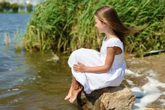 Little girl is sitting on a rock in white dress on sunny day. Little girl is sitting on rock in white dress on sunny day near river stock photography