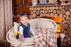 Little girl sitting in rocking chair near fireplace Royalty Free Stock Photo