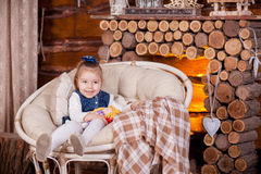 Little girl sitting in rocking chair near fireplace Stock Photo