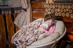 Little girl sitting in rocking chair near fireplace Royalty Free Stock Images
