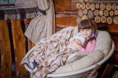 Little girl sitting in rocking chair near fireplace Royalty Free Stock Photography