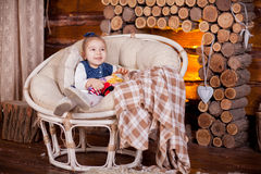 Little girl sitting in rocking near fireplace Royalty Free Stock Photo