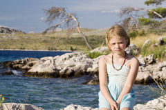 Little girl sitting on a rocks Stock Photography