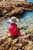Little girl sitting on the rocky shore of the sea Royalty Free Stock Photography