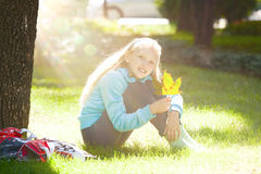 Little Girl Sitting with Rollers and Enjoying Sunny Autumn Day stock photography