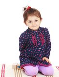 Little girl sitting on the rug in Montessori Stock Photography