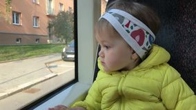 Little girl going by public transport and looking out window. Little girl sitting in running public transport and looking out window to street with curiosity stock video