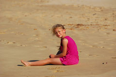 Little girl sitting in sand Stock Photo