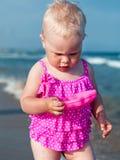Little girl sitting on sand at beach Stock Photos