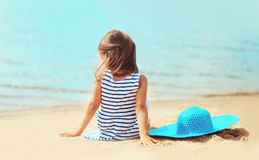 Little girl sitting on the sand beach with straw hat near sea. In summer day Royalty Free Stock Photo