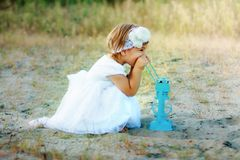 A little girl sitting on the sand near a large lantern. Royalty Free Stock Photography