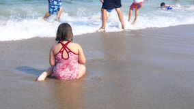 Little girl sitting on the sand by the ocean , the waves splashing in her body. Little girl sitting on the sand by the ocean, the waves splashing in her body stock footage