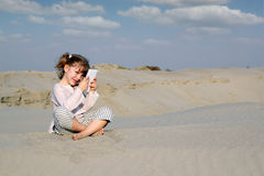 Little girl sitting on sand and play with tablet Stock Photography