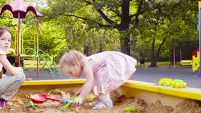 A little girl sitting in a sandbox is picking up sand. Low angle view. A little girl sitting in a sandbox is picking up sand with a scoop in a mold stock footage