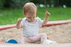 A little girl is sitting in a sandbox royalty free stock photos