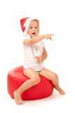 Little girl sitting in santa claus hat Stock Photos