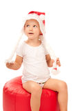Little girl sitting in santa claus hat Stock Images