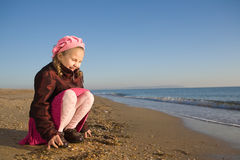 Little girl sitting by the sea Stock Images