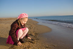 Little girl sitting by the sea Stock Photo