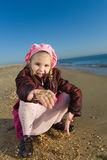 Little girl sitting by the sea Royalty Free Stock Photography