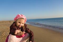 Little girl sitting by the sea. Happy little girl sitting by the sea Royalty Free Stock Photo