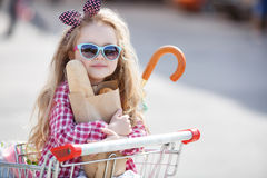 Little girl sitting in shopping trolley Stock Photography