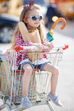 Little girl sitting in shopping trolley Stock Photos