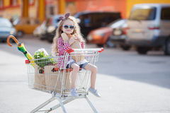 Little girl sitting in shopping trolley Royalty Free Stock Image