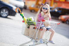 Little girl sitting in shopping trolley Royalty Free Stock Photo