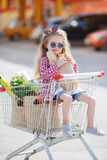 Little girl sitting in shopping trolley Stock Photo