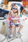 Little girl sitting in shopping trolley Stock Images