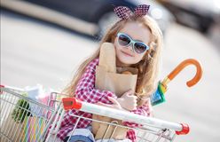 Little girl sitting in shopping trolley Royalty Free Stock Photos