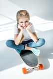 Little girl sitting on skateboard with crossed legs Royalty Free Stock Photography