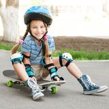 Little girl sitting on a skateboard Royalty Free Stock Image