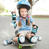 Little girl sitting on a skateboard Royalty Free Stock Images