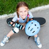 Little girl sitting on a skateboard Royalty Free Stock Photography