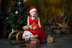 Little girl sitting on a sled with a Christmas tree Royalty Free Stock Photo